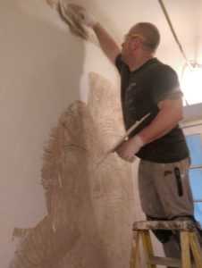 A man on a step ladder plastering a wall in a hallway.In Bristol, England